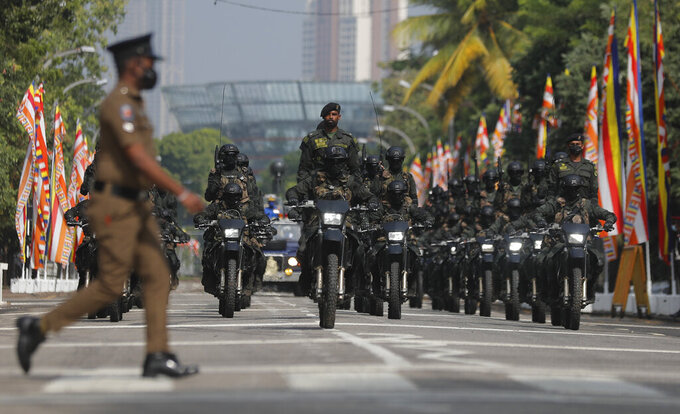 A Sri Lankan police officer walks crosses a road as special force soldiers ride motorbikes during 73rd Independence Day parade rehearsal with a calf elephant in Colombo, Sri Lanka, Wednesday, Feb. 3, 2021. Sri Lanka's independence from British colonial rule is celebrated on Feb. 4 each year. (AP Photo/Eranga Jayawardena)