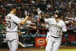 Pittsburgh Pirates' Jordy Mercer, right, celebrates his home run against the Arizona Diamondbacks with Jameson Taillon (50) during the fourth inning of a baseball game Wednesday, June 13, 2018, in Phoenix. (AP Photo/Ross D. Franklin)