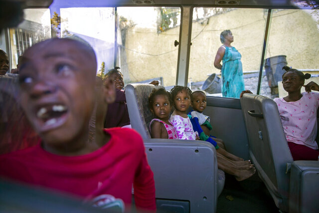 FILE - In this Feb. 14, 2020 file photo, orphans sit inside a social services bus after police removed them from a children's home run by the Orphanage of the Church of Bible Understanding (COBU), following a fire at one of the organization's other homes in Kenscoff, on the outskirts of Port-au-Prince, Haiti. The fire on Feb. 13 killed 13 children and two adult caretakers described  as disabled by authorities and the church's lawyer. (AP Photo/Dieu Nalio Chery, File)