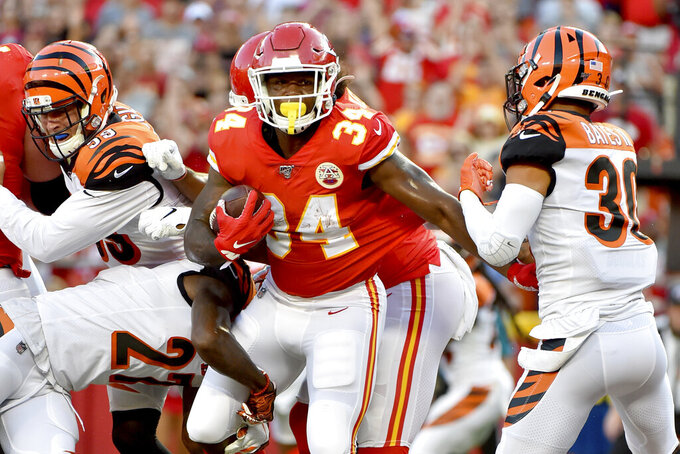 Kansas City Chiefs running back Carlos Hyde (34) scores a touchdown between Cincinnati Bengals defensive back Tony Lippett (39) and Jessie Bates III (30) during the first half of an NFL preseason football game in Kansas City, Mo., Saturday, Aug. 10, 2019. (AP Photo/Ed Zurga)