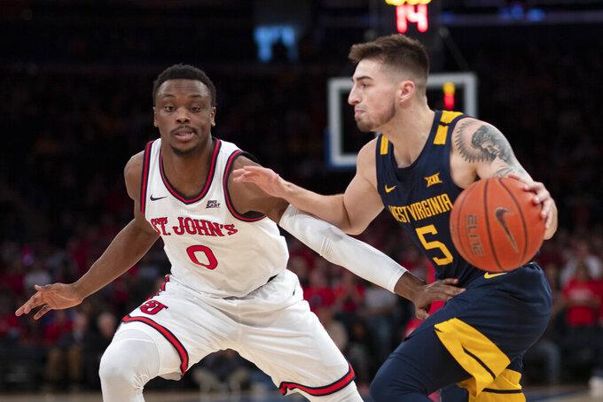 St. John's Mustapha Heron (0) defends against West Virginia's Jordan McCabe (5) in the first half of an NCAA college basketball game Saturday, Dec. 7, 2019 in New York. St. John's won 70-68. (AP Photo/Mark Lennihan)