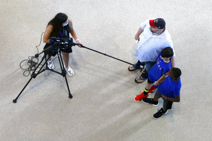 A member of the media uses a long microphone boom to interview Texas Rangers baseball fans during the first day of public tours at Globe Life Field, home of the Texas Rangers baseball team, in Arlington, Texas, Monday, June 1, 2020. The coronavirus pandemic has forced sports teams and their leagues to evaluate how they will welcome back fans. (AP Photo/LM Otero)