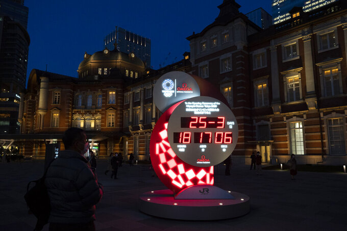 A man looks at a Tokyo 2020 countdown clock displaying the current date and time outside Tokyo Station, Wednesday, March 25, 2020, in Tokyo. Not even the Summer Olympics could withstand the force of the coronavirus. After weeks of hedging, the IOC took the unprecedented step of postponing the world's biggest sporting event, a global extravaganza that's been cemented into the calendar for more than a century. (AP Photo/Jae C. Hong)