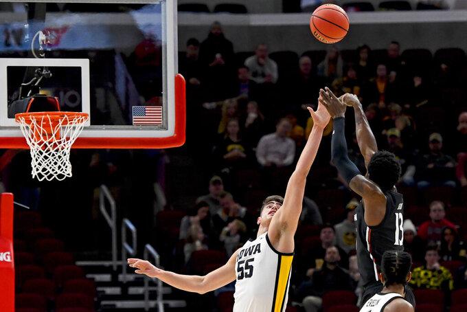 Iowa center Luka Garza (55) defends against a shot by Cincinnati forward Tre Scott (13) during the first half of an NCAA college basketball game Saturday, Dec. 21, 2019, in Chicago. (AP Photo/Matt Marton)
