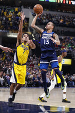Minnesota Timberwolves guard Shabazz Napier (13) shoots next to Indiana Pacers guard Malcolm Brogdon (7) during the first half of an NBA basketball game in Indianapolis, Friday, Jan. 17, 2020. (AP Photo/Michael Conroy)