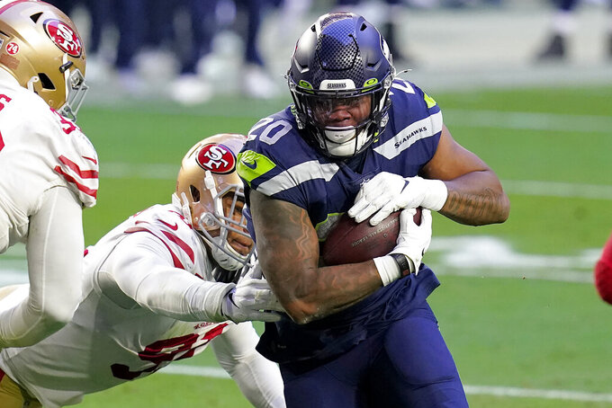 Seattle Seahawks running back Rashaad Penny (20) runs as San Francisco 49ers defensive end Arik Armstead defends during the second half of an NFL football game, Sunday, Jan. 3, 2021, in Glendale, Ariz. (AP Photo/Ross D. Franklin)