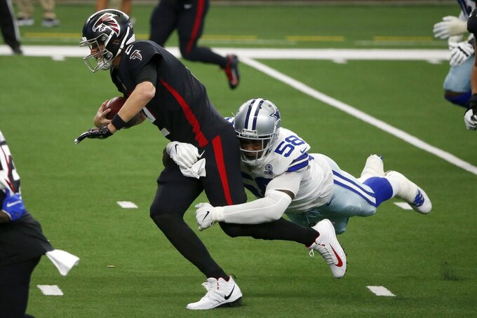 Atlanta Falcons quarterback Matt Ryan scrambles out of the pocket as Dallas Cowboys defensive end Aldon Smith (58) attempts the stop in the first half of an NFL football game in Arlington, Texas, Sunday, Sept. 20, 2020. (AP Photo/Michael Ainsworth)
