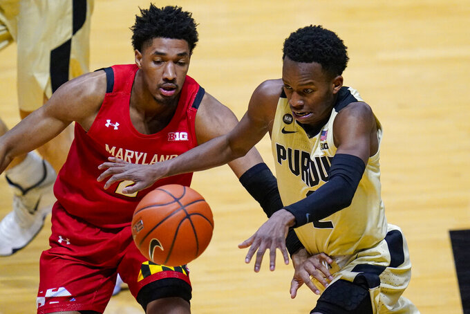 Purdue guard Eric Hunter Jr., right, loses the ball as he drives past Maryland guard Aaron Wiggins (2) during the second half of an NCAA college basketball game in West Lafayette, Ind., Friday, Dec. 25, 2020. (AP Photo/Michael Conroy)