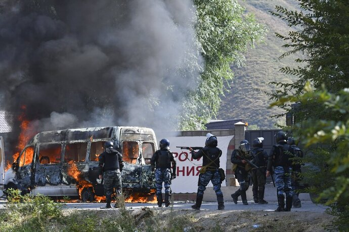 Kyrgyz riot police shoot rubber bullets to stop supporters of former president Almazbek Atambayev, near his residence in the village of Koi-Tash, about 20 kilometers (12 miles) south of the capital, Bishkek, Kyrgyzstan, Thursday, Aug. 8, 2019. Police in Kyrgyzstan detained the Central Asian nation's ex-president Thursday following violent clashes with his supporters, a day after a previous attempt to arrest him left one policeman dead and nearly 80 people injured. (AP Photo/Vladimir Voronin)