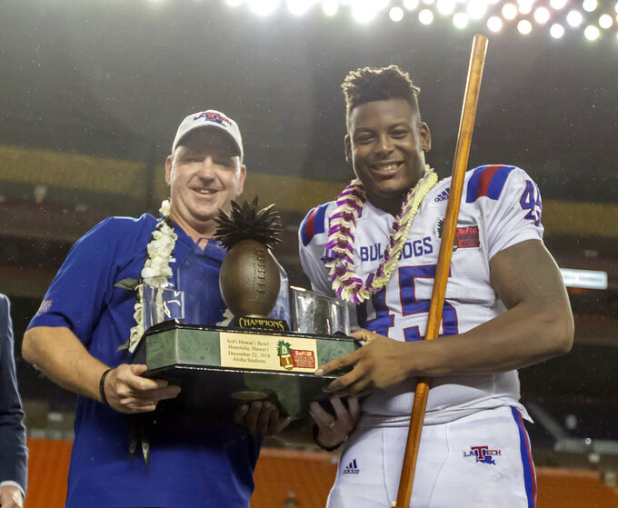 Louisiana Tech head coach Skip Holtz and Louisiana Tech defensive end Jaylon Ferguson (45) hold the Hawaii Bowl Championship trophy after a Hawaii Bowl NCAA college football game against Hawaii, Saturday, Dec. 22, 2018, in Honolulu. Louisiana Tech beat Hawaii 31-14. (AP Photo/Eugene Tanner)