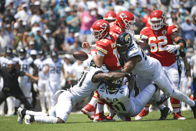 Kansas City Chiefs quarterback Patrick Mahomes (15) fumbles the ball as his is tackled by Jacksonville Jaguars defensive end Yannick Ngakoue, left, defensive end Josh Allen (41) and defensive end Calais Campbell (93) during the first half of an NFL football game, Sunday, Sept. 8, 2019, in Jacksonville, Fla. (AP Photo/Phelan M. Ebenhack)