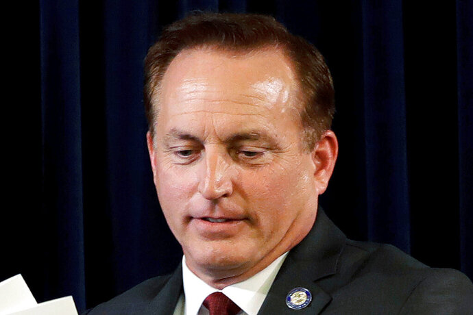 FILE - In this Dec. 19, 2016, file photo, Iowa Secretary of State Paul Pate collects ballots during Iowa's Electoral College vote at the Statehouse in Des Moines, Iowa. Iowa's highest court is upholding a state directive that was used to invalidate tens of thousands of absentee ballot requests mailed to voters pre-filled with their personal information. Pate instructed county elections commissioners in July 2020 that all absentee ballot request forms they mailed to voters must be blank in order to ensure uniformity statewide. Auditors in three counties defied Pate's guidance and courts invalidated their pre-filled forms at the urging of President Donald Trump's campaign. (AP Photo/Charlie Neibergall, File)