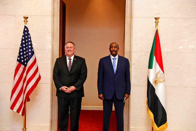 FILE - In this Aug. 25, 2020 file photo, U.S. Secretary of State Mike Pompeo stands with Sudanese Gen. Abdel-Fattah Burhan, the head of the ruling sovereign council, in Khartoum, Sudan.  Sudan's transitional authorities are desperate to have sanctions lifted that are linked to its listing by the U.S. as a terror sponsor. That would be a key step toward ending its isolation and rebuilding its battered economy, which has plunged in recent months, threatening to destabilize the political transition.(Sudanese Cabinet via AP, File)