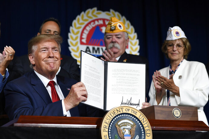 President Donald Trump holds up a presidential memorandum that he signed that discharges the federal student loan debt of totally and permanently disabled veterans following his speech at the American Veterans (AMVETS) 75th National Convention in Louisville, Ky., Wednesday, Aug. 21, 2019. (AP Photo/Susan Walsh)