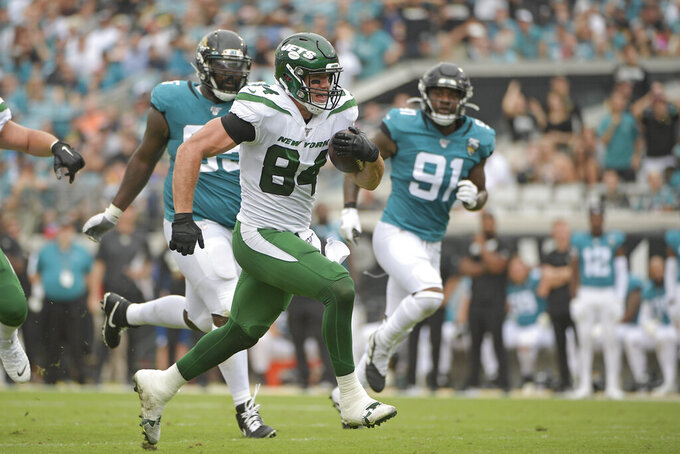 New York Jets tight end Ryan Griffin (84) runs past Jacksonville Jaguars defensive tackle Abry Jones, left, and defensive end Yannick Ngakoue (91) for a touchdown on a 24-yard pass play during the first half of an NFL football game, Sunday, Oct. 27, 2019, in Jacksonville, Fla. (AP Photo/Phelan M. Ebenhack)