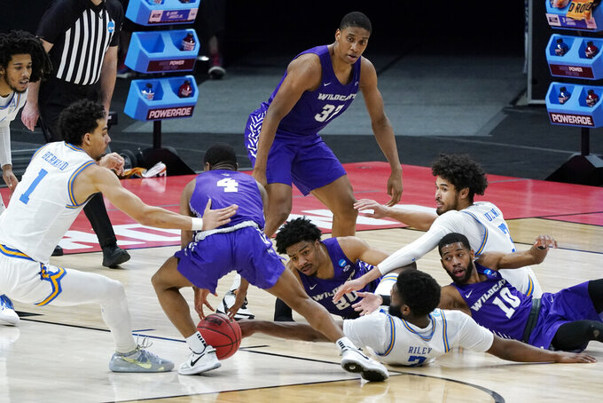 Abilene Christian's Damien Daniels (4) and UCLA's Jules Bernard (1) scramble for a loose ball during the first half of a college basketball game in the second round of the NCAA tournament at Bankers Life Fieldhouse in Indianapolis Monday, March 22, 2021. (AP Photo/Mark Humphrey)