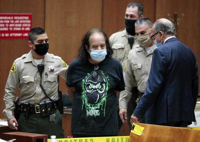 Adult film star Ron Jeremy, second left, with his attorney Stuart Goldfarb, right, makes his first appearance in Dept. 30 at Los Angeles Superior Court in Los Angeles, Tuesday, June 23, 2020. Los Angeles County prosecutors say Jeremy has been charged with raping three women and sexually assaulting a fourth. (Robert Gauthier/Los Angeles Times via AP, Pool)