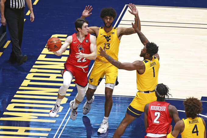 Richmond guard Andre Gustavson (22) passes while defended by West Virginia forwards Isaiah Cottrell (13) and Derek Culver (1) during the second half of an NCAA college basketball game Sunday, Dec. 13, 2020, in Morgantown, W.Va. (AP Photo/Kathleen Batten)