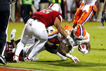 Clemson's Travis Etienne (9) gets taken down short of the goal line by North Carolina State's C.J. Hart (15) during the first half of an NCAA college football game in Raleigh, N.C., Saturday, Nov. 9, 2019. (AP Photo/Karl B DeBlaker)