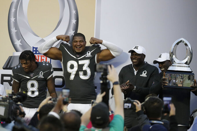 AFC defensive end Calais Campbell, of the Jacksonville Jaguars, (93) and quarterback Lamar Jackson, of the Baltimore Ravens, celebrate at the end of the NFL Pro Bowl football game against the NFC, Sunday, Jan. 26, 2020, in Orlando, Fla. The AFC defeated the NFC 38-33.(AP Photo/John Raoux)