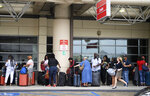 People wait in line at the Southwest counter at the Louis Armstrong Airport in Kenner, La. Friday, July 12, 2019. The system in the Gulf of Mexico is expected to make landfall, possibly as a hurricane, near Morgan City on Saturday morning. (Max Becherer/The Advocate via AP)
