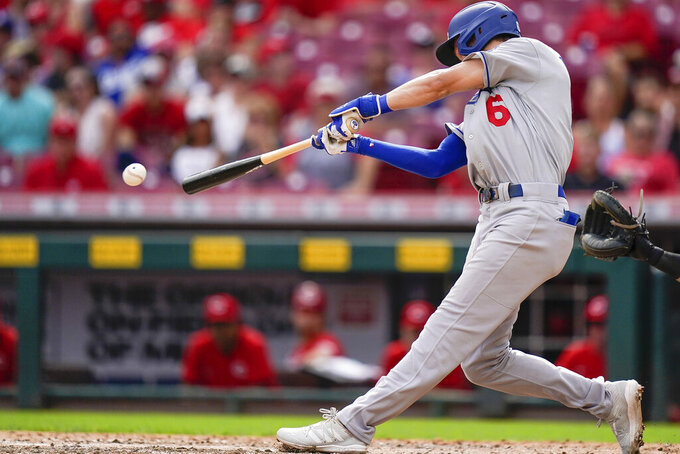 Los Angeles Dodgers' Trea Turner (6) hits a base hit during the ninth inning of a baseball game against the Cincinnati Reds in Cincinnati, Sunday, Sept 19, 2021. (AP Photo/Bryan Woolston)