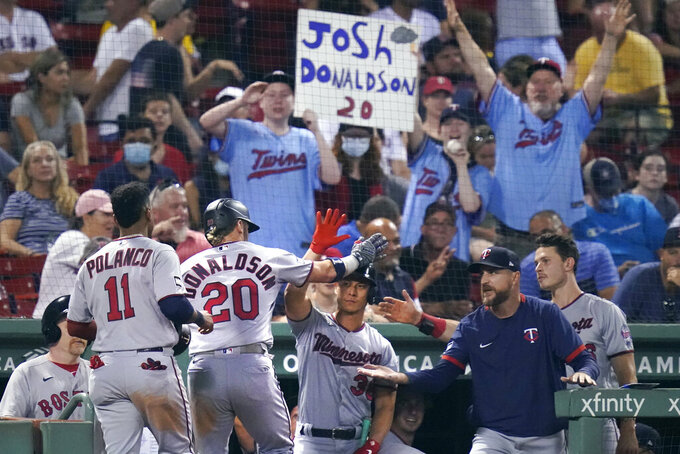 Minnesota Twins' Josh Donaldson (20) is congratulated after his tie-breaking, two-run home run during the 10th inning of a baseball game against the Boston Red Sox at Fenway Park, Wednesday, Aug. 25, 2021, in Boston. (AP Photo/Charles Krupa)