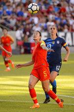 China defender Wu Haiyan and U.S. forward Alex Morgan eye the ball during an international friendly soccer match in Sandy, Utah, Thursday, June 7, 2018. (Trent Nelson/The Salt Lake Tribune via AP)