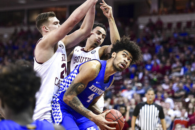 Kentucky forward Nick Richards (4) looks for a shot as South Carolina's Maik Kotsar, left, and Justin Minaya defend during the first half of an NCAA college basketball game Wednesday, Jan. 15, 2020, in Columbia, S.C. (AP Photo/Sean Rayford)