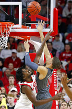 North Carolina State's DJ Funderburk (0) attempts to block the shot of Louisville's Samuell Williamson (10) during the first half of an NCAA college basketball game in Raleigh, N.C., Saturday, Feb. 1, 2020. (AP Photo/Karl B DeBlaker)
