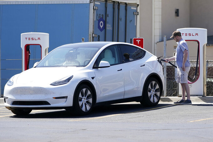 A Tesla owner charges his vehicle at a charging station in Topeka, Kan., Monday, April 5, 2021. The president and the auto industry maintain the nation is on the cusp of a gigantic shift to electric vehicles and away from liquid-fueled cars, but biofuels producers and some of their supporters in Congress aren't buying it. They argue the U.S. should increase sales of ethanol and biodiesel, not abandon them. (AP Photo/Orlin Wagner)