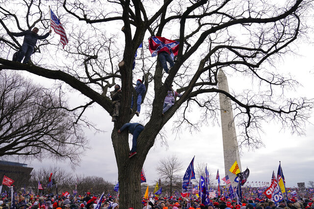 FILE - In this Wednesday, Jan. 6, 2021, file photo, supporters of President Donald Trump participate in a rally in Washington. Both within and outside the walls of the Capitol, banners and symbols of white supremacy and anti-government extremism were displayed as an insurrectionist mob swarmed the U.S. Capitol. (AP Photo/John Minchillo, File)