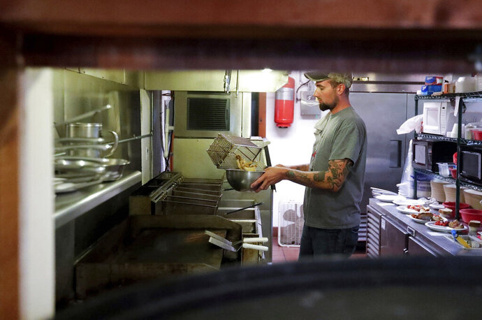 In this Sept. 6, 2019, photo, Sam Stegemann takes the fried perch out of the fryer to serve during the fish fry at Point Beach State Forest concession stand that serves about 100 plates in Two Rivers, Wis. Nothing says Wisconsin more than sitting down to a plate of freshly battered perch and an Old Fashioned on a Friday night. Yet, that happy tradition is getting harder to fulfill in Manitowoc and throughout the state thanks to a plunging supply of fresh lake perch. (Ebony Cox/Herald-Times Reporter via AP)