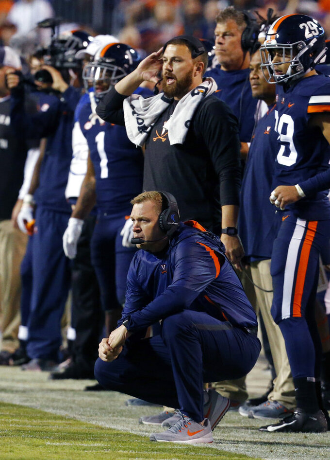 Virginia head coach Bronco Mendenhall, kneeling, watches a field goal attempt during the first half of an NCAA college football game in Charlottesville, Va., Saturday, Oct. 13, 2018. (AP Photo/Steve Helber)