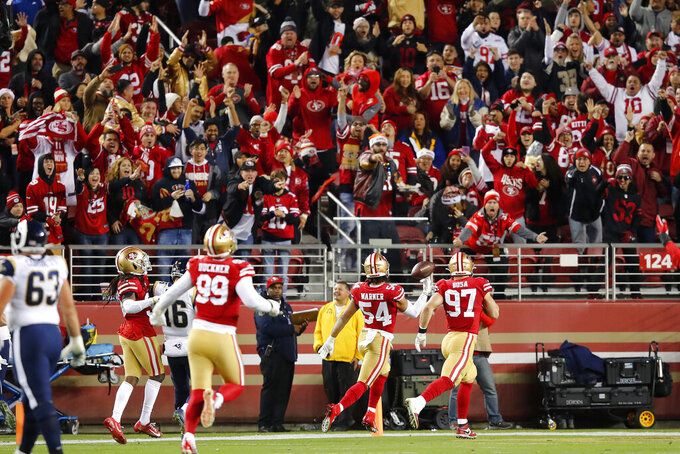Fans cheer as San Francisco 49ers middle linebacker Fred Warner (54) scores on an interception return against the Los Angeles Rams during the first half of an NFL football game in Santa Clara, Calif., Saturday, Dec. 21, 2019. (AP Photo/John Hefti)