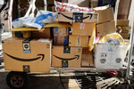FILE - In this Oct. 10, 2018, file photo Amazon Prime boxes are loaded on a cart for delivery in New York. Amazon, which is racing to deliver packages faster, is turning to its employees with a proposition: Quit your job and we'll help you start a business delivering Amazon package. The offer, announced Monday, May 13, 2019, comes as Amazon seeks to speed up its shipping time from two days to one for its Prime members. (AP Photo/Mark Lennihan, File)