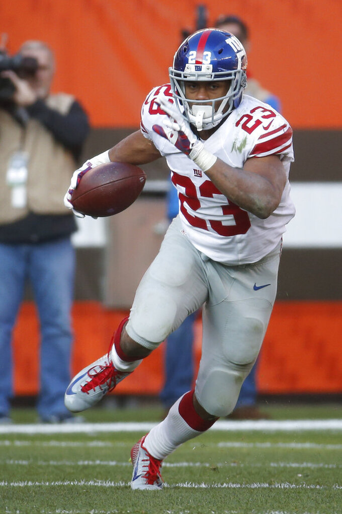FILE - In this Nov. 27, 2016, file photo, New York Giants running back Rashad Jennings carries the ball during the second half of the team's NFL football game against the Cleveland Browns in Cleveland. When Jennings, who retired from pro football after the 2016 season, = got the chance to host World Chase Tag, he was stunned at the athleticism of the participants. No, this is not the brand of tag you played as a kid. (AP Photo/Ron Schwane, File)