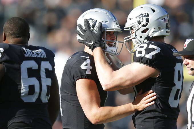 Oakland Raiders quarterback Derek Carr (4) celebrates with tight end Foster Moreau (87) after a touchdown reception by wide receiver Rico Gafford during the first half of an NFL football game against the Tennessee Titans in Oakland, Calif., Sunday, Dec. 8, 2019. (AP Photo/D. Ross Cameron)