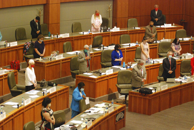 New Mexico House lawmakers hold a moment of silence in memory of COVID-19 victims at the opening of a special sessionon Thursday, June 18, 2020, in Santa Fe, N.M. The legislature met for the first time since the coronavirus pandemic without access by the general public at the state Capitol building. (AP Photo/Morgan Lee)