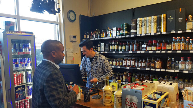 In this Wednesday, Nov. 28, 2019 photo, Andrew Gray, owner of Eddie's Liquor in Edmond, Okla., checks out customer Brien Mikell  after Oklahoma County commissioners earlier in the day voted to ask voters to decide whether liquor stores in the county should be allowed to be open on Sundays. Oklahoma County, the state's largest, became the seventh and last county in the state to meet a deadline to put the question on the March 3 ballot. (AP Photo/Ken Miller)