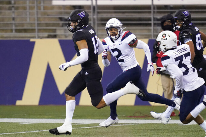Washington's Puka Nacua left, is chased by Arizona's Lorenzo Burns (2) and Jaydin Young (37) on Nacua's 65-yard touchdown pass reception during the first half of an NCAA college football game Saturday, Nov. 21, 2020, in Seattle. (AP Photo/Elaine Thompson)