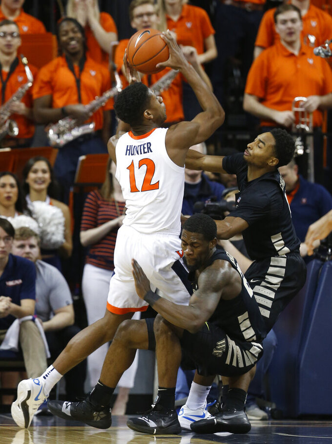 Virginia guard De'Andre Hunter (12) takes a shot as Wake Forest guard Chaundee Brown, bottom, and Wake Forest guard Brandon Childress, right, fall as they defend during the first half of an NCAA college basketball game in Charlottesville, Va., Tuesday, Jan. 22, 2019. (AP Photo/Steve Helber)