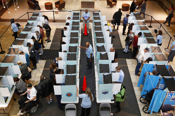 FILE--In this Nov. 6, 2018, file photo, people vote in Henderson, Nev. A court battle has begun in Nevada over a proposal to amend the state constitution and reshape the way voting districts are drawn following the U.S. Census. The head of the League of Women Voters of Nevada said Tuesday, Dec. 3, 2019, she's confident a ballot measure the organization wants to qualify for a statewide vote next November will withstand a lawsuit filed Nov. 26 challenging it as inaccurate and misleading. (AP Photo/John Locher, file)