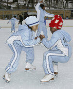 FILE - Eight-year-olds Tatiyana Jenkins, left, and Florence Ngala, members of Figure Skating in Harlem, warm up in a donut spin at Lasker Ice Rink in New York's Central Park in this Saturday, Feb. 7, 2004, file photo. Due to the COVID-19 pandemic, the members of the 24-year-old organization that serves young women of color in New York City didn't see the ice from late winter until fall. The program's objective for nearly a quarter-century has been helping girls of color transform their lives by growing in confidence, leadership and academic achievement. (AP Photo/Ed Bailey, File)