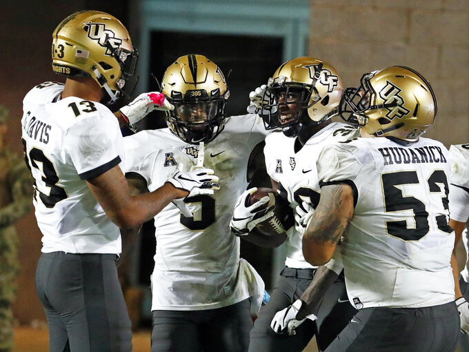 Central Florida's Alex Swenson (30) is congratulated on his touchdown by teammates Dredrick Snelson (5), Bryon Brown (13) and Randy Shannon (53) during the second half of an NCAA college football game against East Carolina in Greenville, N.C., Saturday, Oct. 20, 2018. UCF won 37-10. (AP Photo/Karl B DeBlaker)