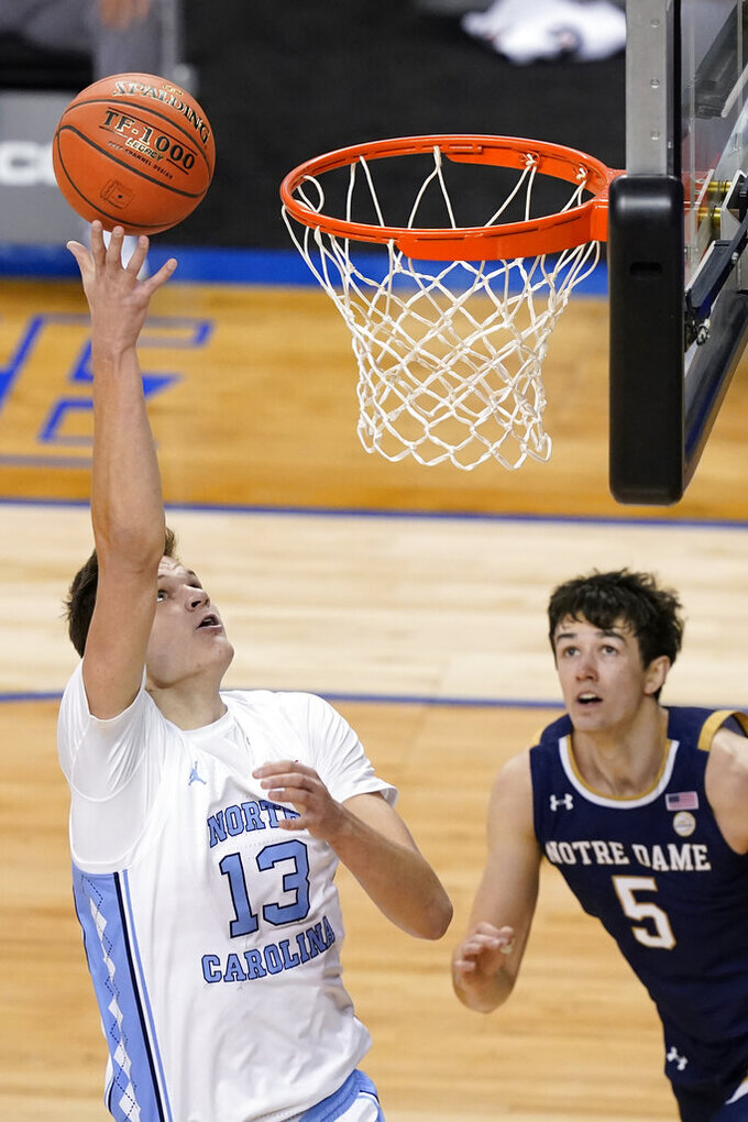 North Carolina forward Walker Kessler (13) takes a shot over Notre Dame guard Cormac Ryan (5) during the first half of an NCAA college basketball game in the second round of the Atlantic Coast Conference tournament in Greensboro, N.C., Wednesday, March 10, 2021. (AP Photo/Gerry Broome)