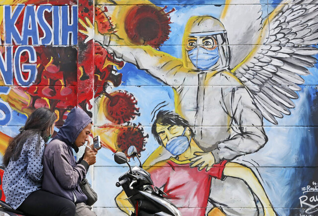 A motorist stops to light up a cigarette near a mural honoring honoring health care workers during the new coronavirus outbreak on the outskirts of Jakarta, Indonesia, Tuesday, June 2, 2020. (AP Photo/Dita Alangkara)