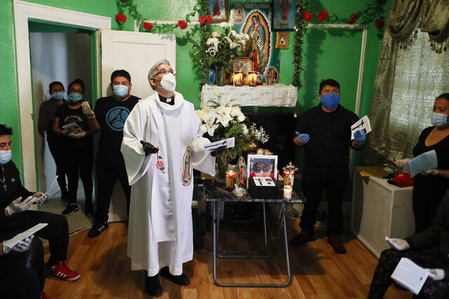 The Rev. Fabian Arias performs an in-home service beside the remains of Raul Luis Lopez who died from COVID-19 the previous month, Saturday, May 9, 2020, in the Corona neighborhood of the Queens borough of New York. (AP Photo/John Minchillo)