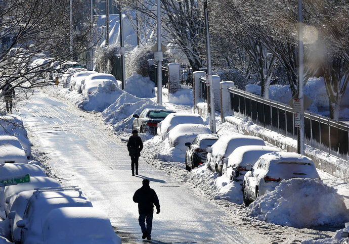 People walk past rows of snow-covered cars on Marginal Street in Boston, Wednesday, March 14, 2018. The Boston area was hit with it's third nor'easter of the month on Tuesday, a storm that brought powerful gusts of wind. (AP Photo/Michael Dwyer)