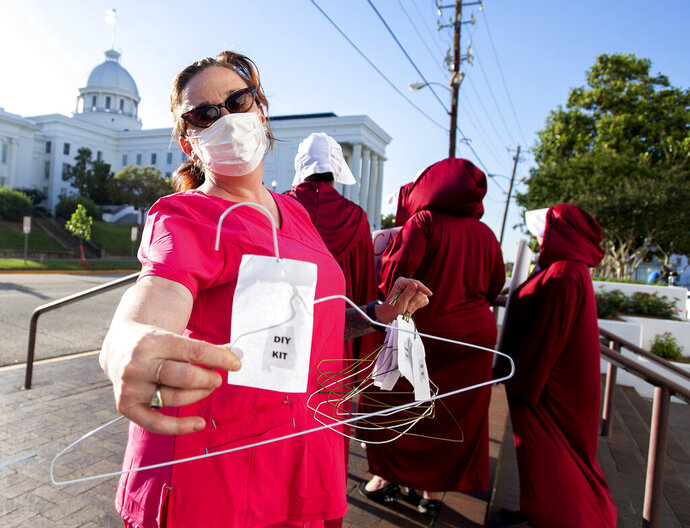 Laura Stiller hands out coat hangers as she talks about illegal abortions during a rally against a ban on nearly all abortions outside of the Alabama State House in Montgomery, Ala., on Tuesday, May 14, 2019. The legislation would make performing an abortion a felony at any stage of pregnancy with almost no exceptions. (Mickey Welsh/The Montgomery Advertiser via AP)